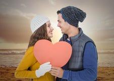 Couples romantiques tenant un coeur et semblant face à face sur la plage Images libres de droits