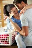 Couples romantiques triant la blanchisserie dans la cuisine Image stock