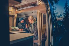 Couples RV Camping. Couples and the RV Park Camping. Young Couples Planning Next Trip in the Motorhome royalty free stock image