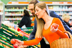 Couples sélectionnant des fruits dans l'hypermarché Photographie stock