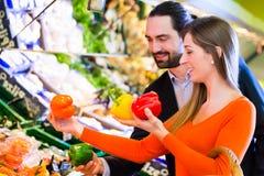 Couples sélectionnant des légumes dans l'hypermarché Photo stock