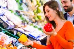Couples sélectionnant des légumes dans l'hypermarché Images stock