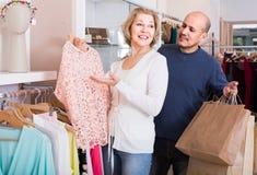Couples sélectionnant le chemisier rose dans le magasin d'habillement Photos stock