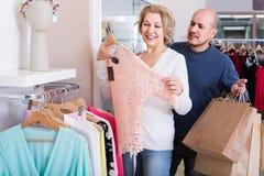 Couples sélectionnant le chemisier rose dans le magasin d'habillement Images libres de droits