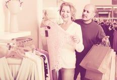Couples sélectionnant le chemisier rose dans le magasin d'habillement Photos libres de droits