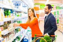 Couples sélectionnant les produits refroidis dans l'hypermarché Image libre de droits
