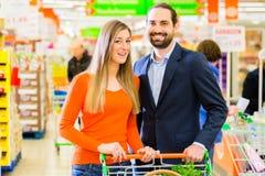 Couples sélectionnant les produits refroidis dans l'hypermarché Photos stock