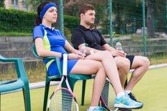 Couples sérieux des joueurs de tennis ayant un repos et une observation Image stock