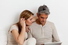 Couples sérieux utilisant l'ipad Image stock