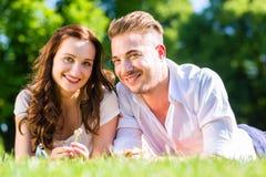 Couples s'étendant sur apprécier de pelouse de parc Photos stock