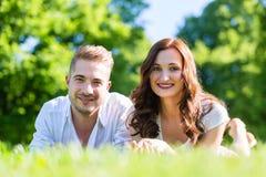 Couples s'étendant sur apprécier de pelouse de parc Photos libres de droits