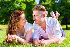 Couples s'étendant sur la pelouse de parc appréciant le soleil Image libre de droits