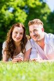 Couples s'étendant sur la pelouse de stationnement Photos stock