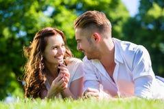 Couples s'étendant sur le parc Photo libre de droits