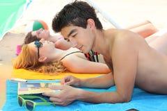 Couples s'étendant sur une plage Photo libre de droits