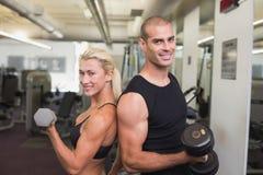 Couples s'exerçant avec des haltères dans le gymnase Image stock