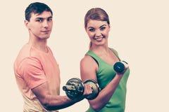 Couples s'exerçant avec des haltères soulevant des poids Photographie stock libre de droits