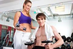 Couples s'exerçant en gymnastique avec des poids Images libres de droits