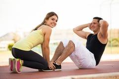 Couples s'exerçant ensemble dehors Photographie stock libre de droits