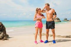 Couples s'exerçant ensemble sur la plage Photographie stock