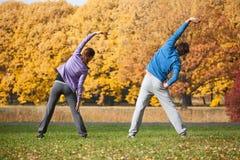 Couples s'exerçant en parc dans la chute Photos libres de droits