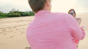 Couples sains attrayants ayant l'amusement fonctionnant ensemble sur la plage clips vidéos