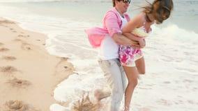 Couples sains attrayants ayant l'amusement fonctionnant ensemble sur la plage banque de vidéos