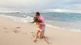 Couples sains attrayants ayant l'amusement fonctionnant ensemble sur la plage