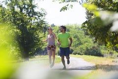 Couples sains, convenables et folâtres fonctionnant en parc Images libres de droits