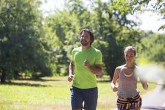 Couples sains, convenables et folâtres fonctionnant en parc Photo libre de droits
