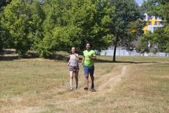 Couples sains, convenables et folâtres fonctionnant en parc Photos stock