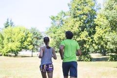 Couples sains, convenables et folâtres fonctionnant en parc Photographie stock