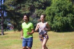 Couples sains, convenables et folâtres fonctionnant en parc Image libre de droits