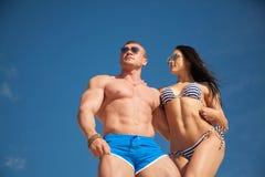 Couples sains d'ajustement sur le fond de ciel photographie stock