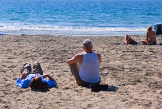 Couples on sandy beach. Rear view of two couples sat on sandy beach with sea in background Stock Images