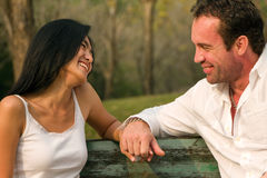 Couples sat hand in hand and smile stock photography