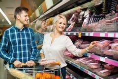 Couples satisfaisants de famille choisissant la viande réfrigérée image stock