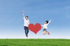 Couples sautant avec la carte de coeur Photo stock