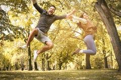 Couples sautant dans la taille Amusement en stationnement Photos libres de droits