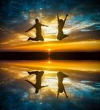 Couples sautant dans le coucher du soleil Images stock