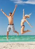 Couples sautant sur la plage Photos libres de droits