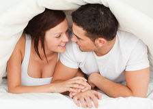 Couples se cachant sous une couverture Image stock