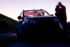 Couples se penchant sur un véhicule Photographie stock