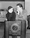 Couples se penchant sur une radio et regardant l'un l'autre (toutes les personnes représentées ne sont pas plus long vivantes et  Photo libre de droits