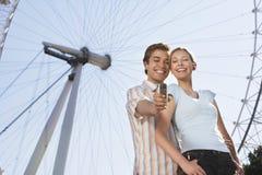 Couples se photographiant contre l'oeil de Londres Photos libres de droits