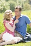 Couples se reposant à l'extérieur retenant le sourire de fleur Images stock