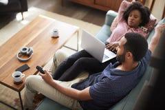 Couples se reposant à l'ordinateur de Sofa At Home Using Laptop et à la TV de observation photographie stock libre de droits