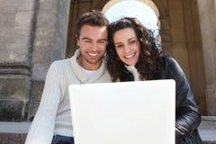 Couples se reposant avec un ordinateur portatif Photo libre de droits