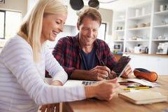Couples se reposant dans leur cuisine utilisant l'ordinateur portable Photos stock