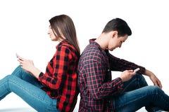 Couples se reposant de nouveau au dos et à l'aide des téléphones Photographie stock